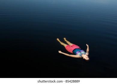 Woman Floating in Dark Blue Lake