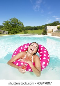 Woman floating in an inner tube in a swimming pool and laughing with drink in hand. Vertical.