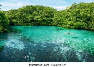 Woman floating in a nature cenote in Riviera Maya, Mexico