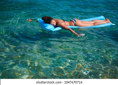 Woman floating on air bed and smiling while holding hands in water