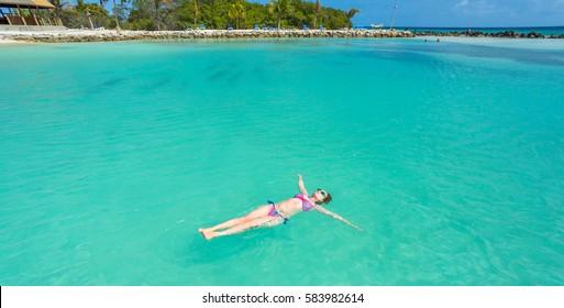 Woman floating on a back in the beautiful sea. Aruba island