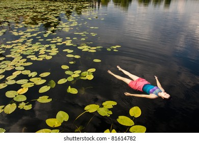 Woman Floating on Lake with Lily Pads