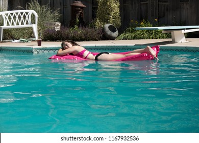 Woman floating on a raft laying on her stomach on a pink raft wearing a pink and black bikini in a backyard outdoor swimming pool. Woman floating in a swimming pool on a pink raft in a backyard.