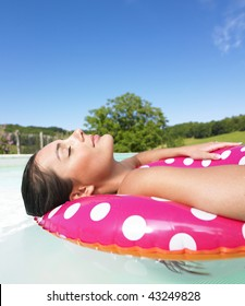 Woman floating in a pink polka dot inner tube with eyes closed. Vertical.