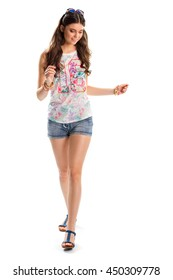 Woman in floral tank top. Short denim shorts and sandals. Top with pink number print. Cute model wears casual apparel.