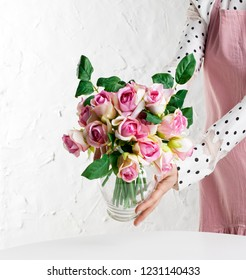 Woman florist creating beautiful rose bouquet in flower shop. Working in flower studio, making decorations and arrangements.
