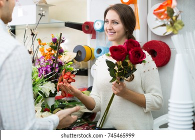 Woman florist helping to pick floral bouquet of flowers