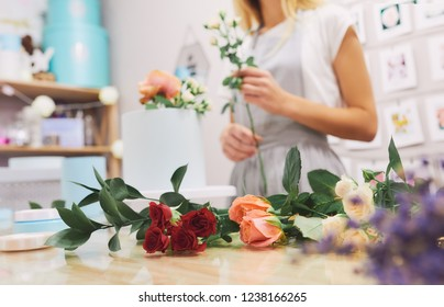 A woman florist makes a bouquet in a box. On the table lie flowers roses. She takes the flower.
