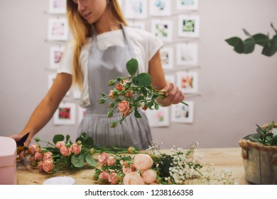 A woman florist makes a bouquet. On the table lie flowers roses. Girl with scissors cuts the rose.
