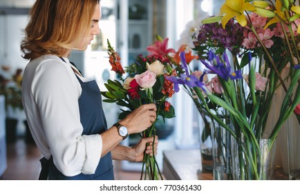 Woman florist preparing a bouquet with fresh flowers at her shop. Woman working at flower shop making bouquet.