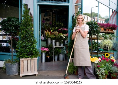 Woman florist standing at the entrance to her shop, leaning on a broom