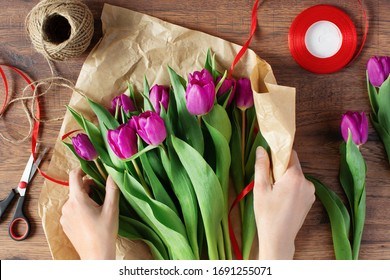 Woman florist wrapping bouquet of amazing purple tulips in craft paper on wooden table top view.