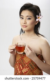 A woman with a flower in her hair holding a cup of tea