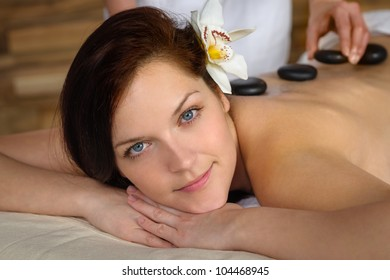Woman with flower at spa having hot stone back treatment