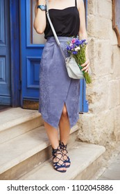 Woman with flowers in blue suede leather sandals on the stairs. Woman with handbag wearing black top, trendy long suede skirt and gladiators sandals. Fashionistaon the city street, summer fashion look