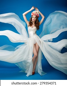 Woman with flowers on her head in a white dress on a blue background