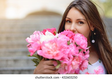 Woman with flowers peonies outdoors