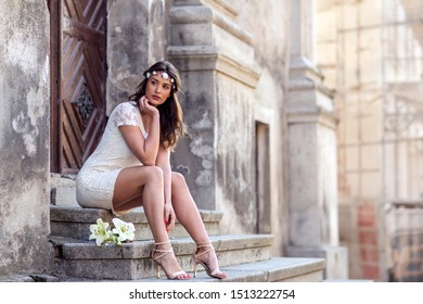 Woman with flowers sitting at the stairs in old town