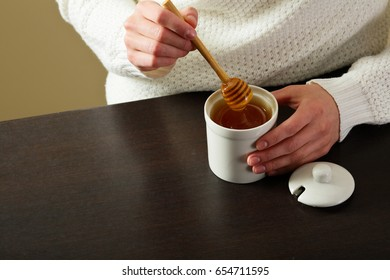 Woman flowing honey with spoon in hands