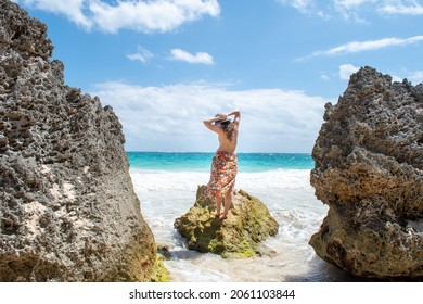 A woman in a flowy orange skirt stands on the rock on the beach in Tulum, white sands and blue water