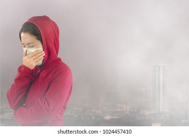 """Woman with flu sneezing, woman dressed pink in winter clothing wearing mask to her nose in a cold and flu health concept against """"Toxic dust"""" covered the city of Bangkok has a health effect."""