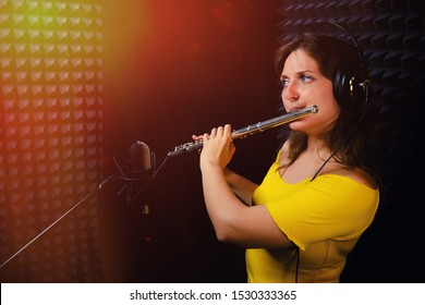 Woman flutist playing the silver flute. Record wind musical instruments with a professional microphone. Girl flute player plays in music studio.