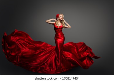 Woman in Fluttering Red Dress, Waving Silk Cloth, Artistic Fashion Model in Flowing Silk Fabric on gray background