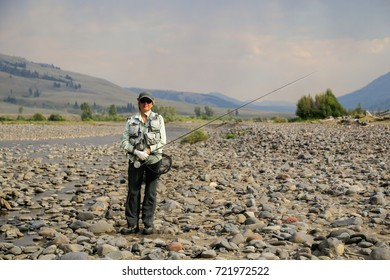 A woman fly fisher in Yellowstone National Park