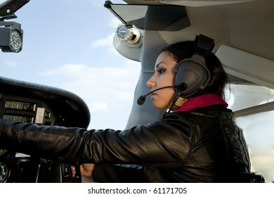 A woman is flying an airplane and messing with the instruments