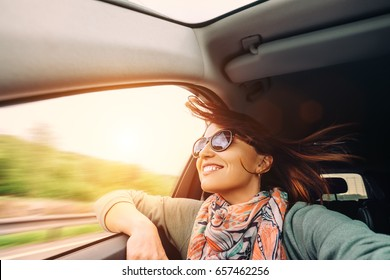 Woman with flying hair looks from car window