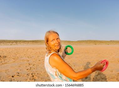 Woman flying kite on beach - Cap Ferret, France