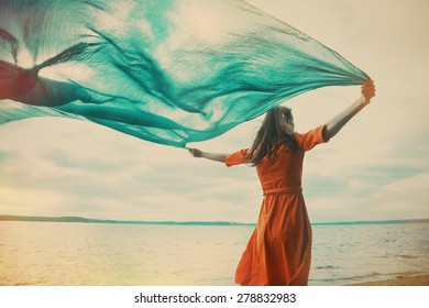 woman with flying silk blue scarf on the beach, instagram filtered