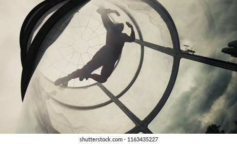 Woman flying in a wind tunnel. Indoor skydiving wind tunnel. Extreme parachuting