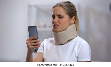 Woman in foam cervical collar reading message on cellphone, feeling pain in neck