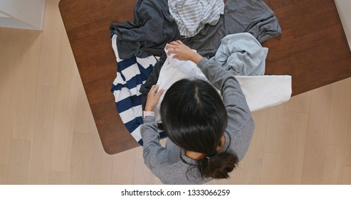 Woman fold clothes at home