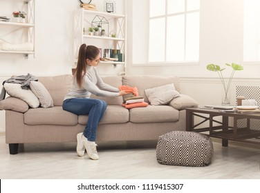 Woman folding clean t-shirts, sitting on sofa at home. Young girl tidying up clothes after laundry or shopping, copy space
