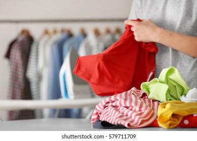 Woman folding clothes after ironing, closeup
