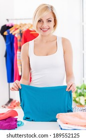 Woman folding clothes. Beautiful blond hair woman folding clothes and smiling at camera