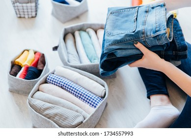 Woman folding clothes, organizing stuff in baskets and boxes. Concept of clothes storage, minimalism lifestyle and japanese t-shirt folding system. Tidy up in wardrobe