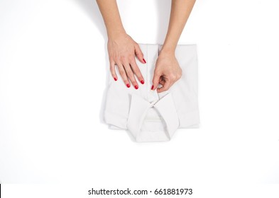 Woman folding clothes. Top view on white background with copy space. Female hands folding white, elegant mans shirt.