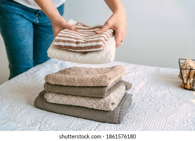 Woman folding clothes and towels in bedroom, organizing laundry in boxes and baskets. Concept of minimalist lifestyle and japanese konmari folding system. Tidy up wardrobe