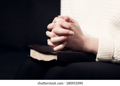 Woman folding hands over her holy bible and praying to God.
