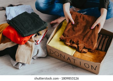 Woman folding and packing clothes into cardboard donation box. Concept of volunteering work, donation and clothes recycling. Helping poor people