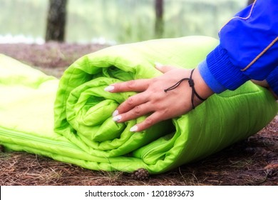 A woman folds and packs a sleeping bag, going on a journey through the forest. The concept of tourism and ecotourism. Equipment for traveling.