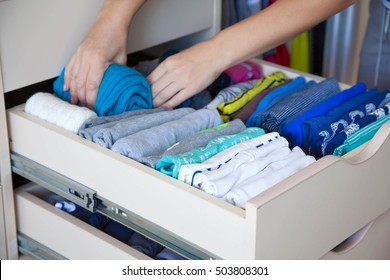 The woman folds t-shirts in the drawer. A woman is tidying up the closet. Vertical storage of clothing.