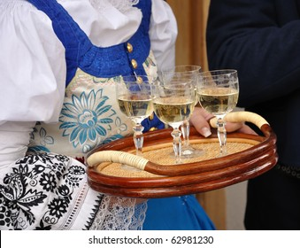 Woman in folk costume is holding plate with glass of wine