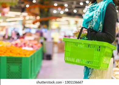 Woman with food basket at grocery store or supermarket