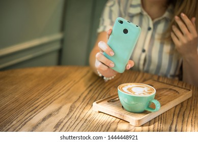 Woman food blogger shoots content with a cup of cappuccino in a cafe at a wooden table. turquoise color. lifestyle concept.