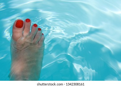 Woman foot in blue water, concept of summer and relax.