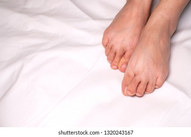Woman foot flexion on bed sheets color white